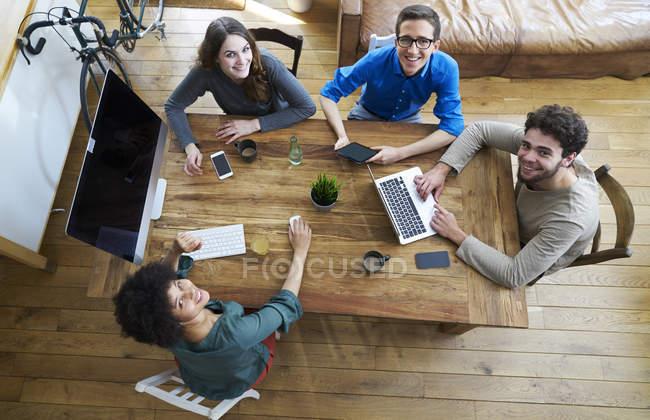 Повышенный вид улыбающихся коллег, работающих вместе за деревянным столом в офисе — стоковое фото