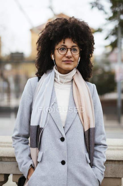 Retrato de mujer con auriculares de pie en la ciudad - foto de stock