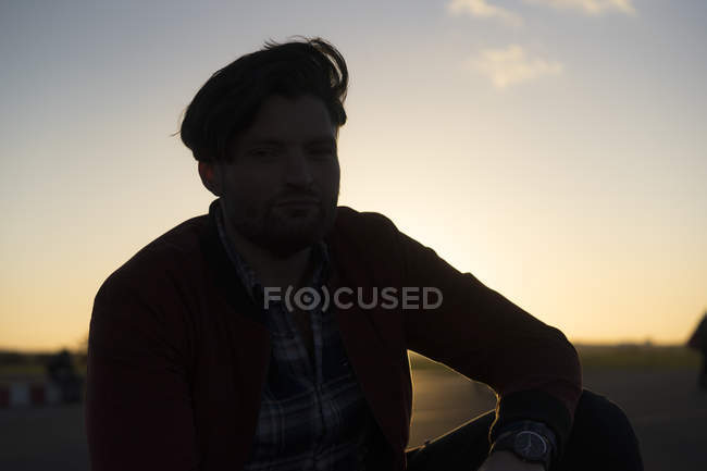 Portrait of young man outdoors at sunset — Stock Photo