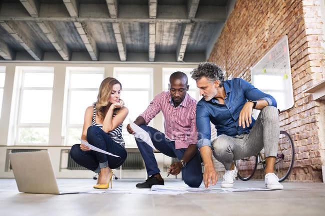 Команда архітекторів, обговорюючи відновлення мансардного офісу — стокове фото