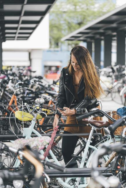 Giovane donna con bicicletta utilizzando il telefono cellulare in città — Foto stock