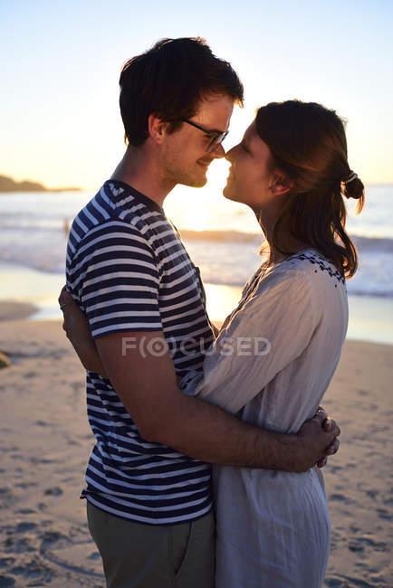 Романтическая пара на пляже на закате — стоковое фото