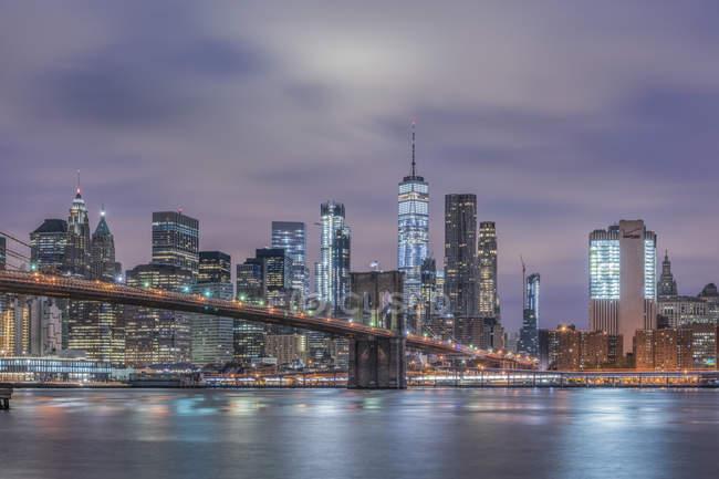 Estados Unidos, Nueva York, Manhattan, Brooklyn, paisaje urbano con Brooklyn Bridge por la noche - foto de stock