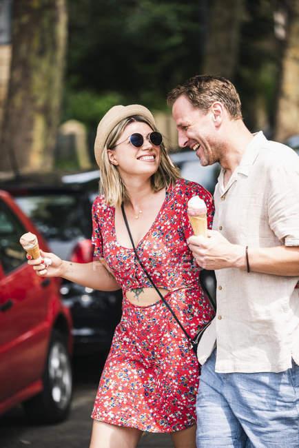 Casal feliz com cones de sorvete andando na cidade — Fotografia de Stock