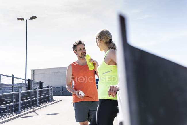 Fit couple jogging en la ciudad, divirtiéndose, tomando un descanso. - foto de stock