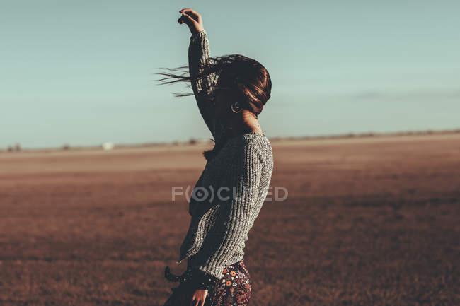 Junge Frau mit wehenden Haaren steht in Wüstenlandschaft — Stockfoto