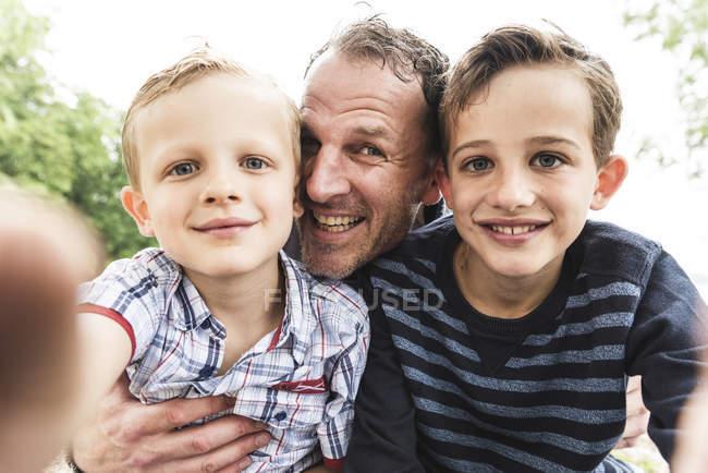 Selfie di padre felice con due figli all'aperto — Foto stock
