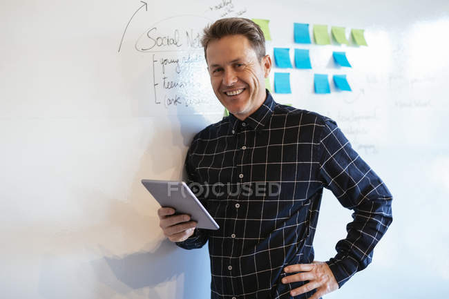 Smiling businessman with tablet in office leaning against whiteboard — Stock Photo