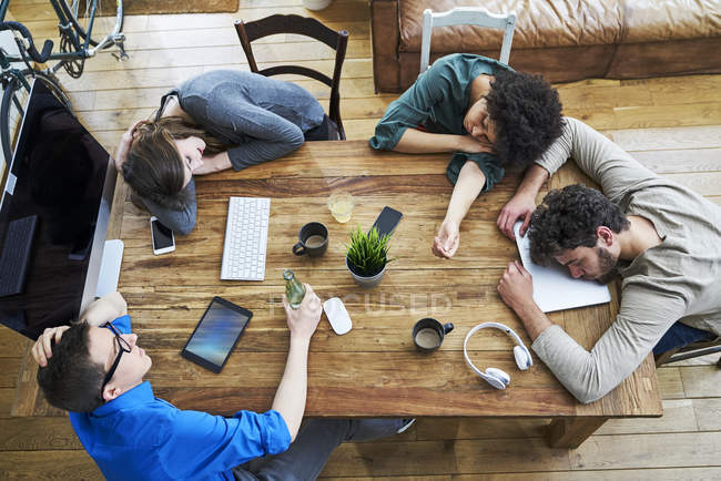 Elevated view of exhausted coworkers at wooden table in office — Stock Photo