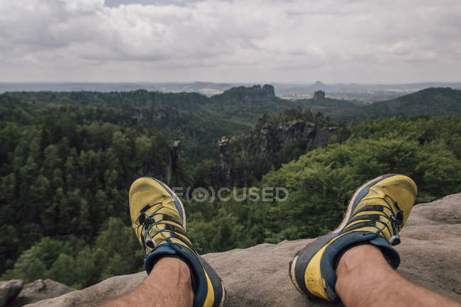 Germany, Saxony, Elbe Sandstone Mountains, man's feet on a hiking trip sitting on rock — Stock Photo