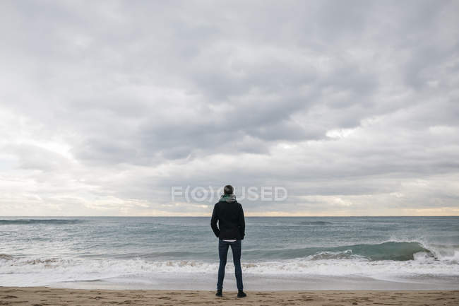 Back view of man standing on the beach in winter and looking at distance — Stock Photo