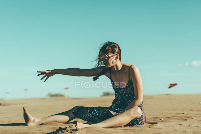 Young woman sitting in desert landscape reaching out her hand — Stock Photo