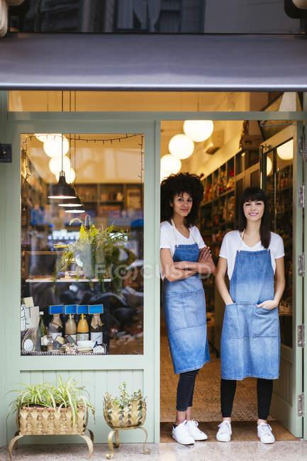 Портрет двух улыбающихся женщин, стоящих у входной двери магазина — стоковое фото