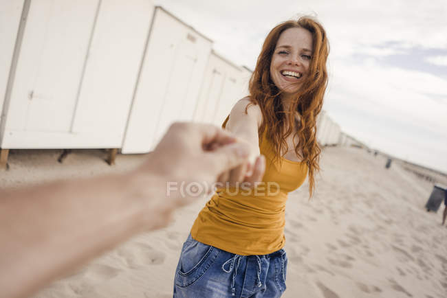 Smiling woman reaching out to man's hand — Stock Photo