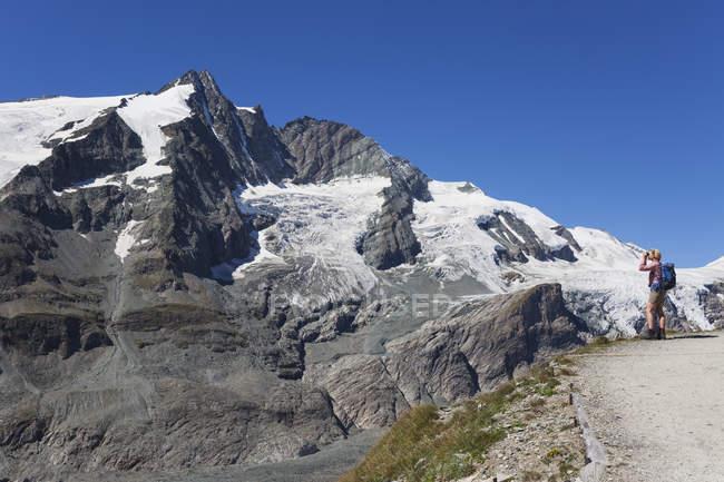 Австрія, Каринтія, жінка - туристка з біноклем спостерігає за вершиною Гросгсґлокнера, національним парком Високого Тауерна. — стокове фото