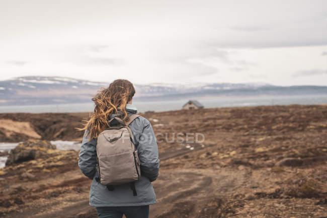 Islande, vue de dos d'une femme avec sac à dos randonnée dans le paysage — Photo de stock