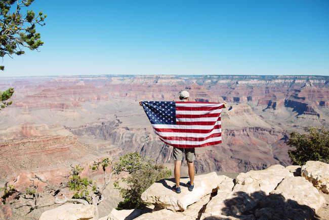 USA, arizona, Rückansicht eines Mannes mit amerikanischer Flagge mit Blick auf den Grand Canyon Nationalpark — Stockfoto