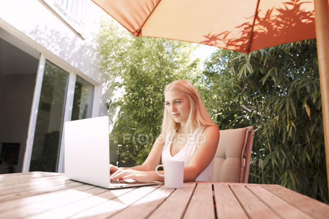 Young woman using laptop, sitting on garden table — Stock Photo