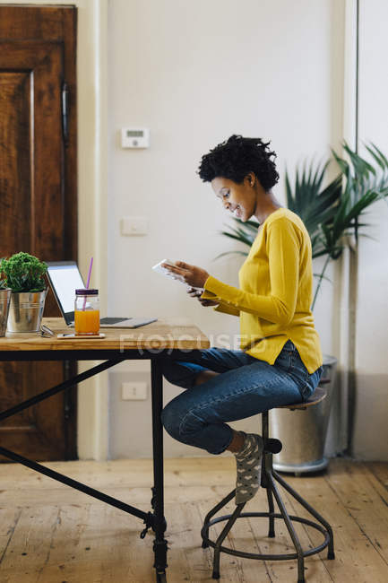 Young african american woman sitting at home and reading on digital tablet — Stock Photo