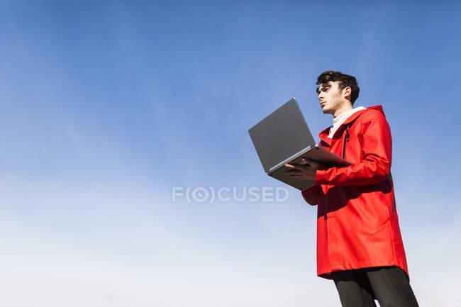 Молодий чоловік, який використовує ноутбук проти блакитного неба. — стокове фото