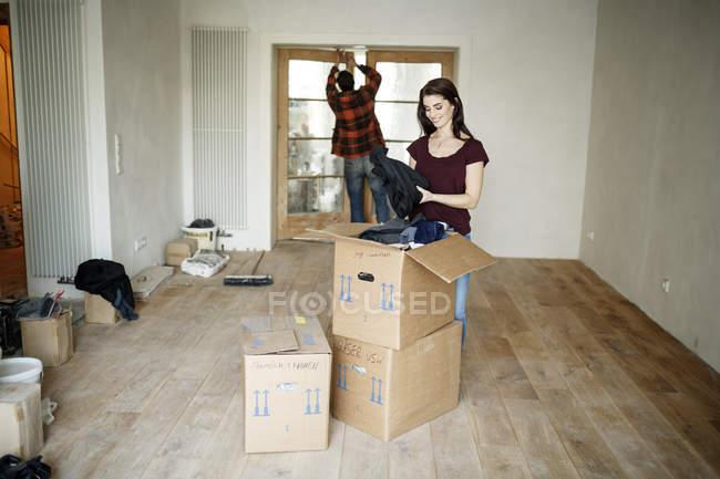 Pareja mudándose a su nuevo hogar, mujer desempaquetando cajas - foto de stock