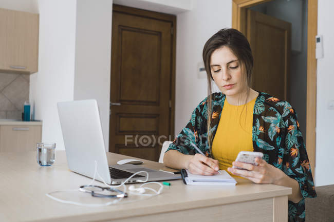 Jeune femme assise à table à la maison en utilisant un téléphone cellulaire et un ordinateur portable prenant des notes — Photo de stock
