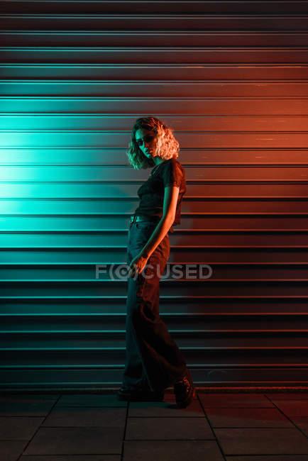 Jeune femme élégante la nuit devant un volet roulant, portant des lunettes de soleil — Photo de stock