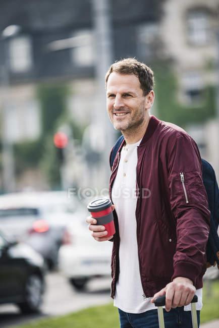 Uomo sorridente con valigia rotolante e caffè da asporto in città — Foto stock