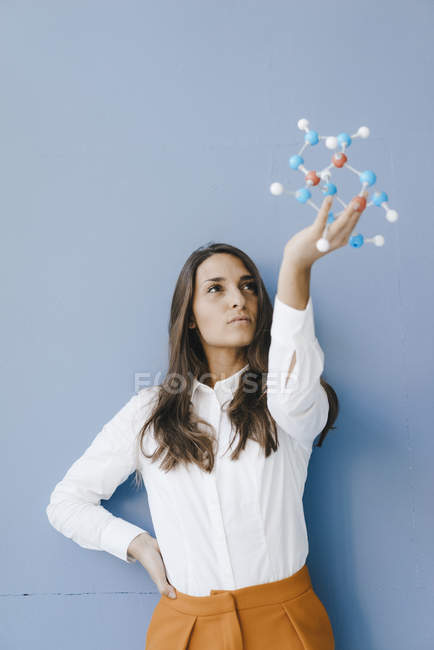 Female scientist holding molecule model, looking for solutions — Stock Photo