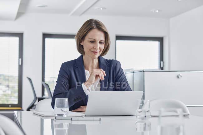 Безробітна жінка використовує ноутбук у офісі. — стокове фото
