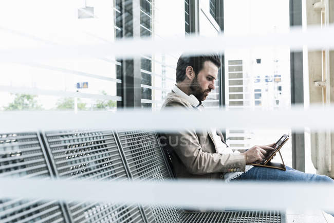 Young man using tablet at the station platform — Stock Photo