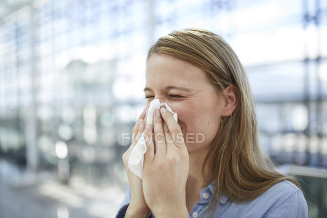 Mujer joven que sopla la nariz - foto de stock