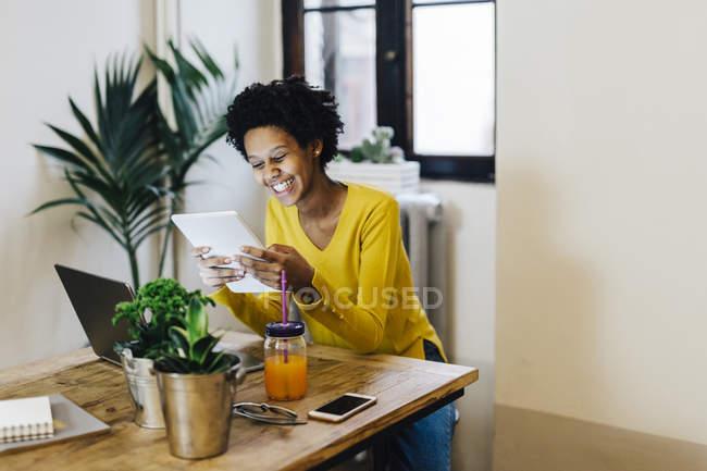 Молодая африканская американка сидит за столом с несколькими переносными устройствами — стоковое фото