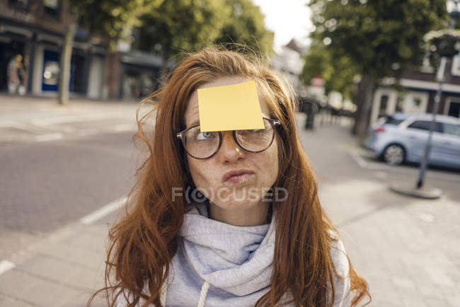 Redheaded woman with adhesive note sticking on her forehead — стоковое фото