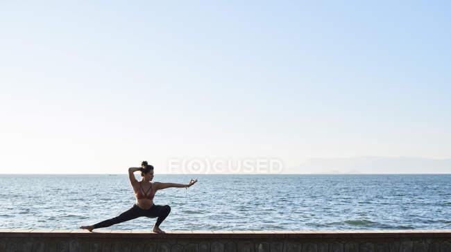 Молодая женщина практикует йогу на стене у моря — стоковое фото