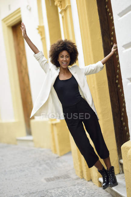 Spain, Cadiz, portrait of fashionable young woman with curly hair in front of house — Stock Photo
