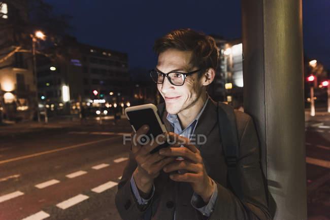 Uomo d'affari sorridente utilizzando il telefono cellulare sulla strada urbana di notte — Foto stock