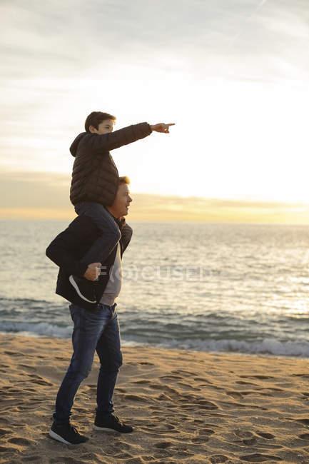 Père portant son fils sur les épaules sur la plage pendant le coucher du soleil — Photo de stock