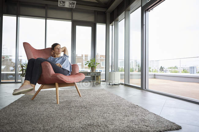 Woman sitting in armchair at home relaxing — Stock Photo