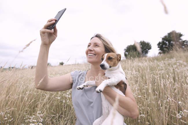 Женщина с собакой делает селфи со смартфоном на поле — стоковое фото