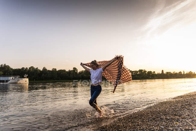 Young woman walking barefoot on riverside with blanket — Stock Photo