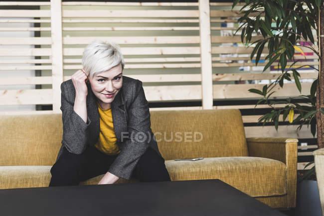 Portrait de femme d'affaires décontractée souriante assise sur le canapé dans le salon — Photo de stock