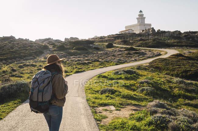 Italia, Cerdeña, mujer en un viaje de senderismo hacia el faro - foto de stock