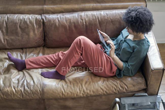 Junge Frau liegt auf Couch und benutzt Tablet — Stockfoto