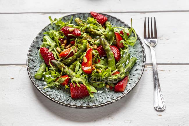 Salada de espargos verdes, foguetes, morangos e pinhões — Fotografia de Stock