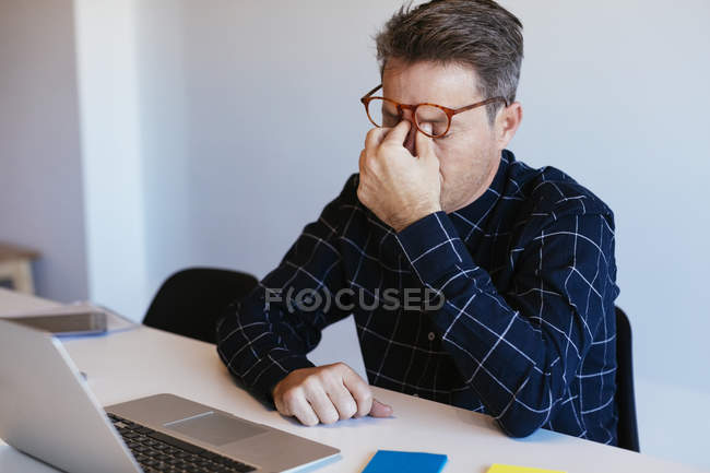 Businessman at desk in office rubbing his eyes — Fotografia de Stock