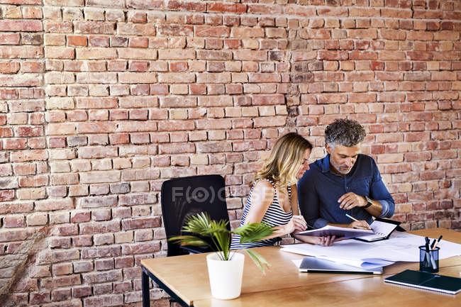 Colleagues with plan and notebook working at desk in office — Stock Photo