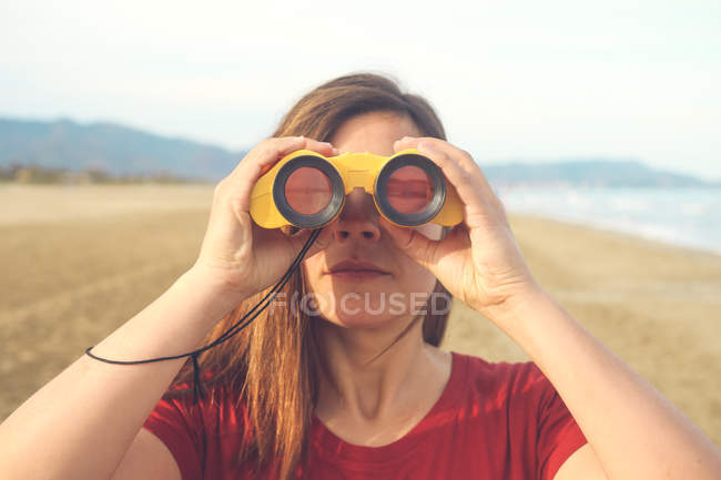 Woman using binoculars on the beach — Stock Photo