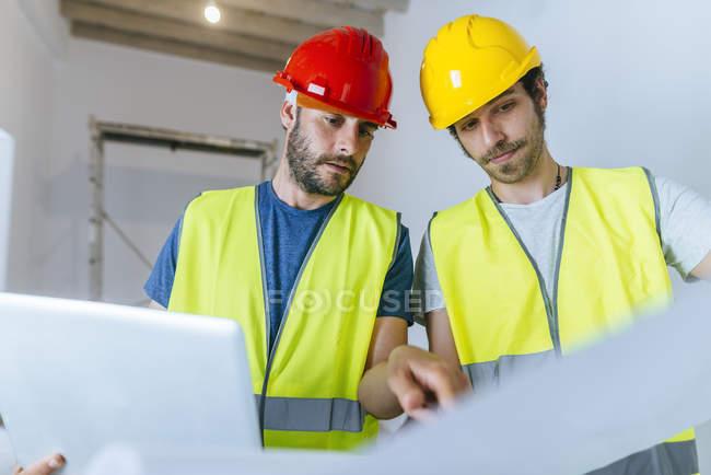 Працівники працюють з ноутбуком і планують на будівельному майданчику. — стокове фото