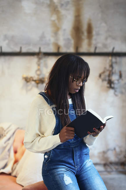 Young woman reading book at home — Stock Photo